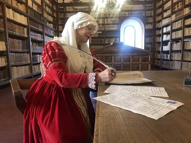 Mujer disfrazada de medieval escribiendo con pluma